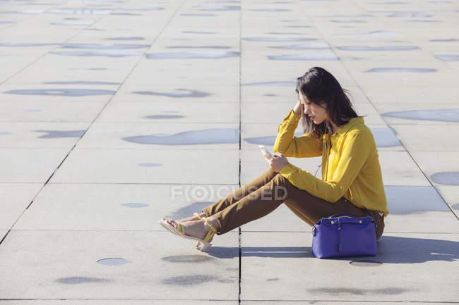 Vista lateral de alegre jovem chinesa sentada no chão com smartphone — Fotografia de Stock