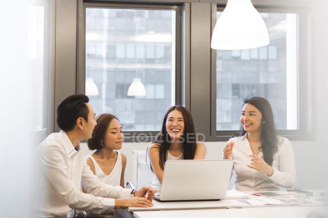 Молодые азиатские коллеги, работающие в современном офисе — стоковое фото