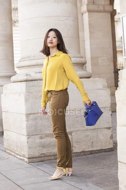 Молодая китаянка ходит с синей сумкой — стоковое фото