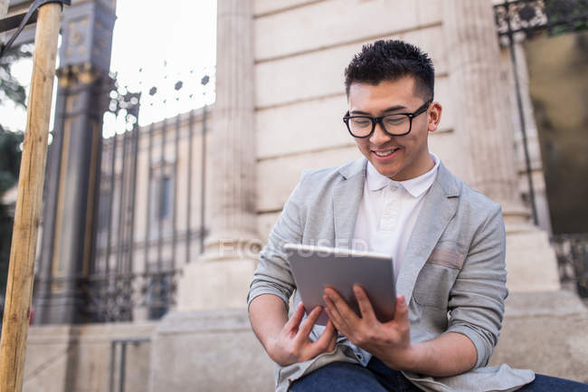 Cheerful chinese businessman with a tablet computer in the street, Spain — Stock Photo