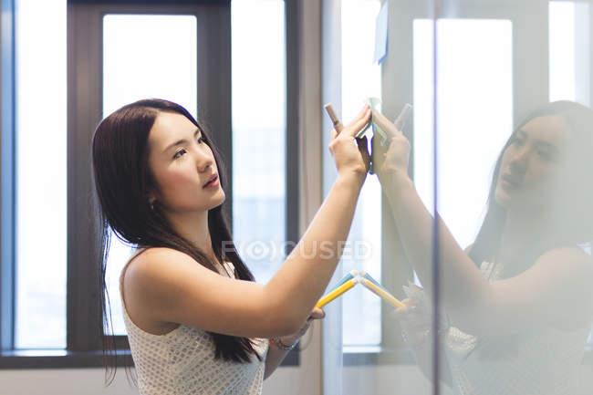 Молода жінка вставлення пост це на борту в сучасні офісні — стокове фото