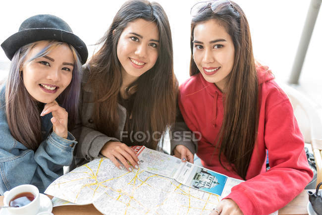 Young women looking at the camera with map, Spain — стоковое фото