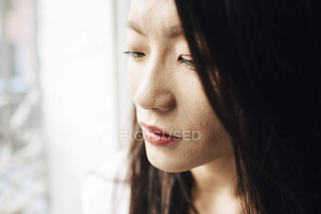 Attractive asian woman looking out of window — Stock Photo
