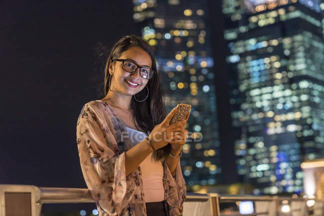 Giovane donna giocare con il suo smartphone in città urbana — Foto stock