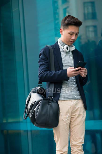 Jeune Chinois décontracté utilisant un téléphone et un casque dans la rue, Espagne — Photo de stock