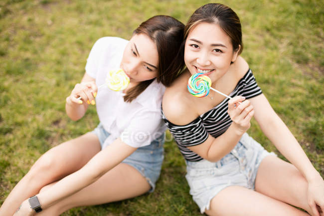 Teen asians girlfriends with candies having fun in the park — Stock Photo