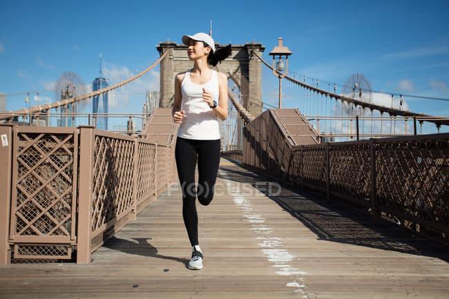 Довольно азиатская бегунья тренируется на открытом воздухе, работая на Бруклинском мосту с Манхэттеном, Нью-Йорк на заднем плане . — стоковое фото