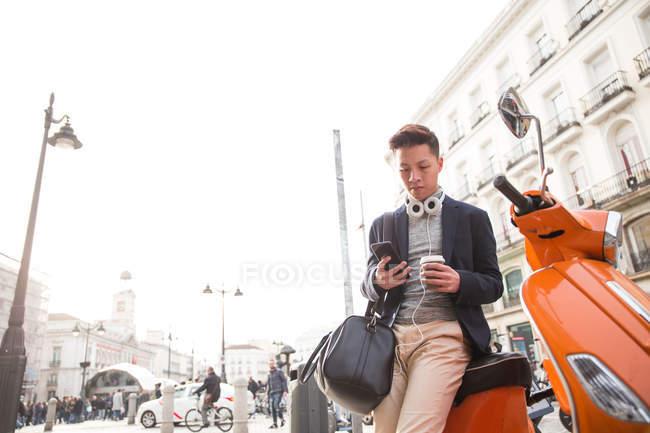 Hombre chino joven casual con un teléfono inteligente. auriculares y una taza de café en la Puerta del Sol, Madrid, España - foto de stock