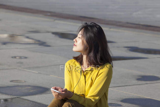 Joyeuse jeune femme chinoise assise sur le sol à écouter de la musique — Photo de stock