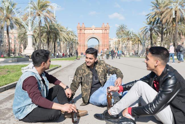 Amigos indianos turista beber cerveja sentada no chão em Arco de tríplice Barcelona Espanha — Fotografia de Stock