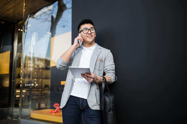 Cheerful chinese businessman talking on the phone in the street and holding a tablet computer, Spain — Stock Photo