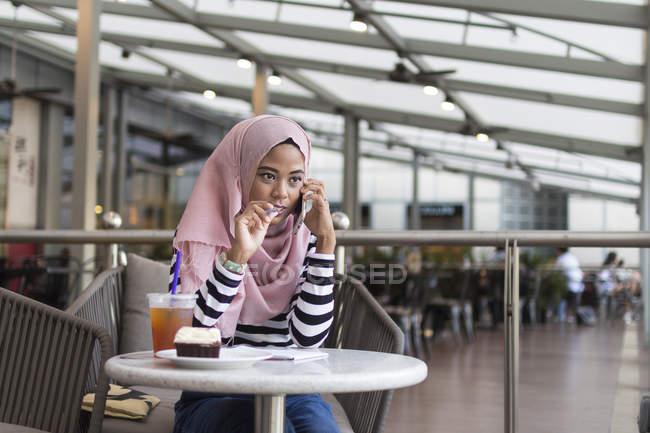 Jovem mulher anotar algumas informações em um Cafe — Fotografia de Stock