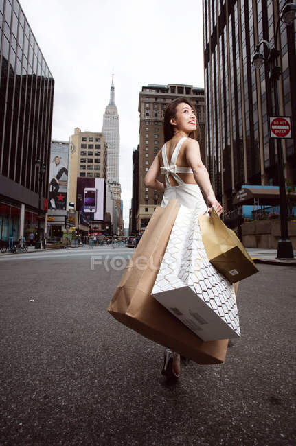 A beautiful elegant woman walking passing street and holding shopping bags with Empire state building. — Stock Photo
