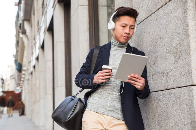 Casual young chinese man with a tablet ,headphones, and a cup of coffee in Madrid, Spain — Stock Photo