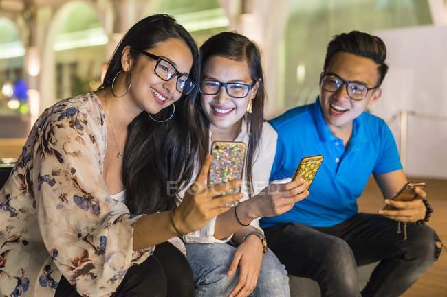 Молодые красивые азиатские друзья, использующие смартфоны на открытом воздухе — стоковое фото