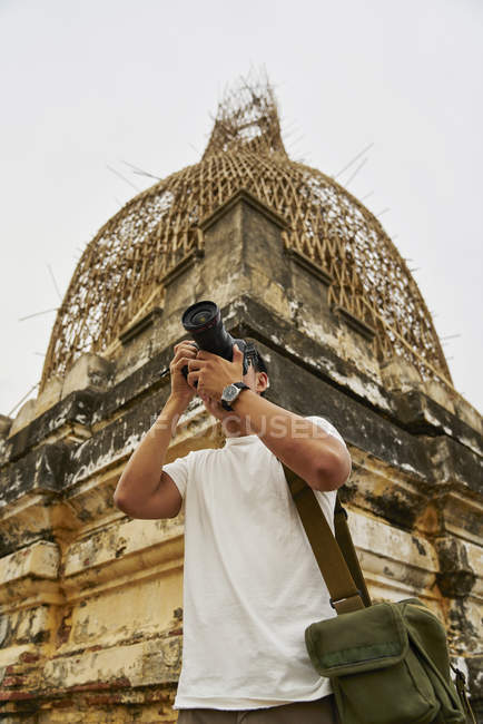 Joven tomando fotos en la pagoda Shwesandaw, Bagan, Myanmar - foto de stock