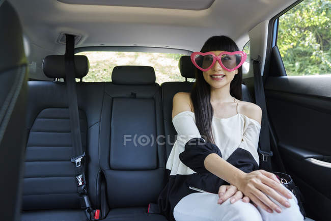 Young woman with party glasses in the back seat of a car — Stock Photo