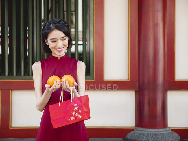 Chinese woman holding oranges and looking down — Stock Photo