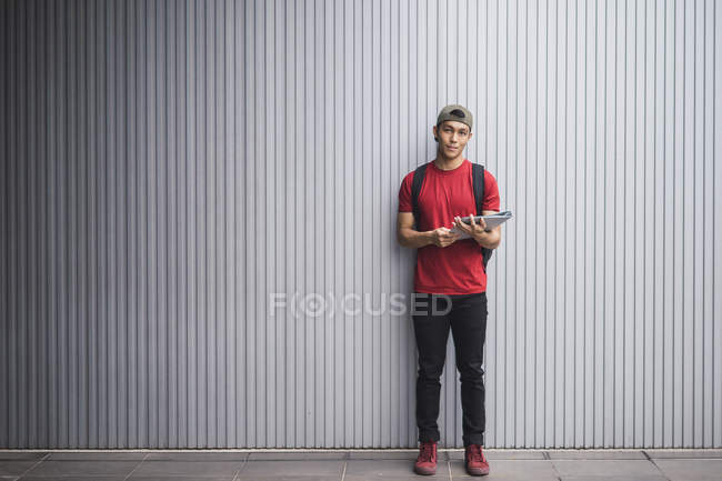 Молодой студент азиатского колледжа, держащий документы у стены — стоковое фото