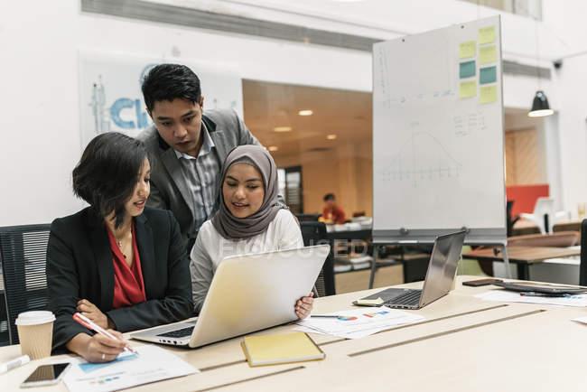 Молодые мультикультурные бизнесмены, работающие с ноутбуками в современном офисе — стоковое фото