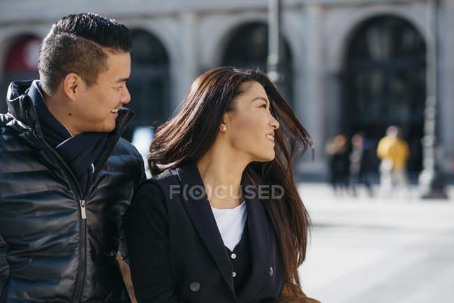 Dos turistas chinos paseando por la plaza de la ópera y el teatro real de Madrid, España. - foto de stock
