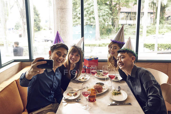 Happy young asian friends celebrating christmas together in cafe and taking selfie — Stock Photo