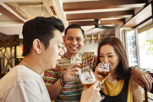 Happy young asian friends together in bar with beer — Stock Photo