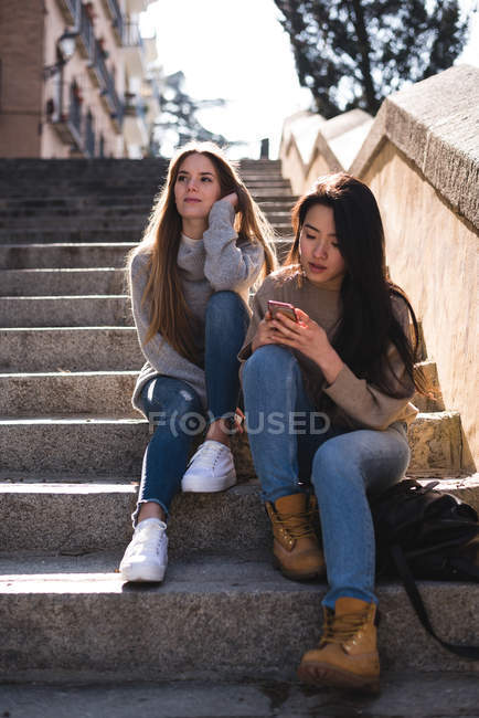 Two beautiful female friends using smartphone on stairs in city — Stock Photo