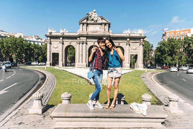 Японские и китайские путешественницы, стоящие и позирующие в Puerta de Alcala в Мадриде, Испания . — стоковое фото