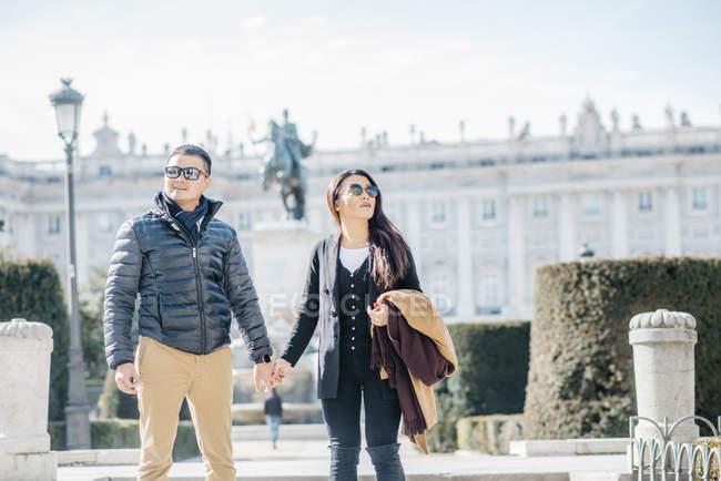 Pareja de chinos paseando por la almudena ana palacio real en Madrid, España - foto de stock