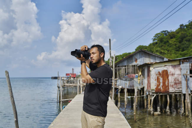 Young photographer taking photos at Ban Ao Yai Fishing Village — Stock Photo