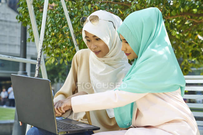 Two beautiful women in a Tudung working on a laptop — Stock Photo