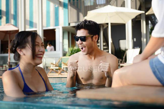 Beaux jeunes amis asiatiques se détendre dans la piscine — Photo de stock