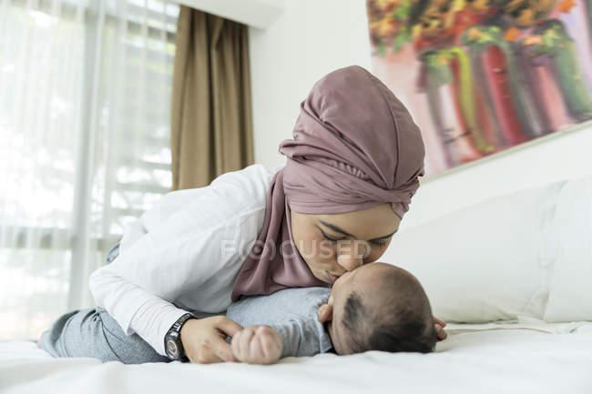 Asiatico musulmano madre baci bambino su letto — Foto stock