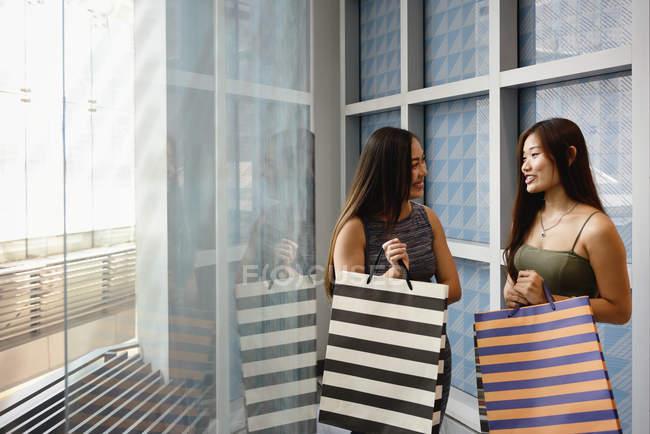 Dos mujeres asiáticas con bolsas de compras en centro comercial - foto de stock