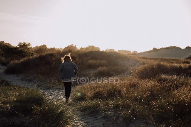 Junge Frau Wandern auf Ebenen — Stockfoto