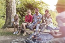 Family and friends roasting sausages at the campfire — Stock Photo