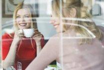 Sourire des jeunes femmes au café — Photo de stock