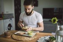 Young man having breakfast — Stock Photo