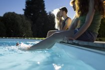 Friends sitting by poolside — Stock Photo