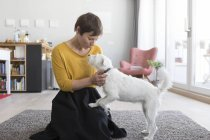 Woman sitting on floor and playing with dog — Stock Photo