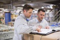 Мужчины проверяют документы на заводе — стоковое фото