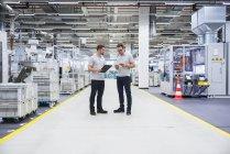 Uomini in piedi e parlando in fabbrica — Foto stock