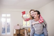Happy young couple in new home taking selfie — Stock Photo