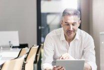Бізнесмен, сидячи в офісі і використання планшетного — стокове фото
