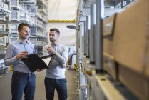 Men with folder standing in warehouse — Stock Photo