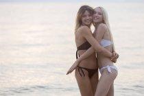 Jovens mulheres abraçando na praia — Fotografia de Stock