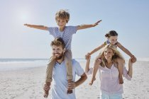 Bambini seduti sulle spalle dei genitori — Foto stock