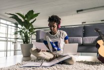 Молодая женщина сидит дома с наушниками, ноутбуком и документами — стоковое фото
