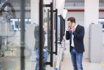 Homme à l'aide de téléphone en usine — Photo de stock